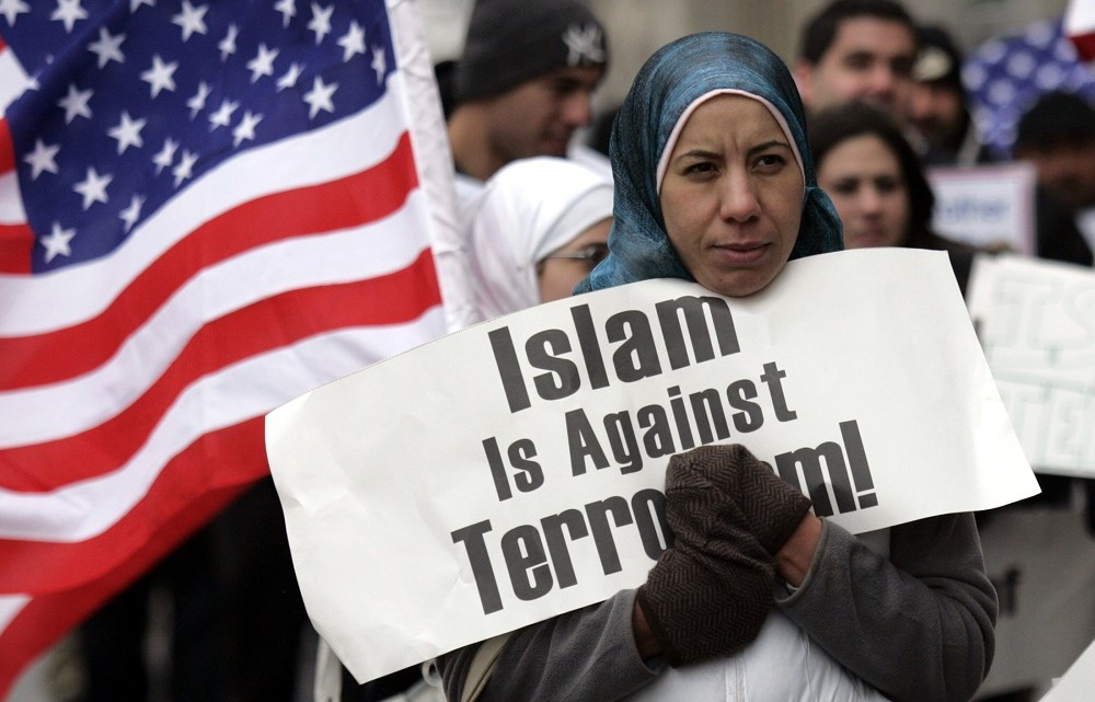 Arab-Americans hold signs as they demonstrate outside the Federal court building in Detroit, Michigan